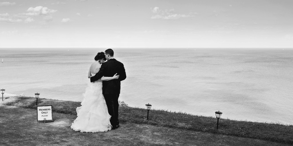 Black and white image of bride and groom standing on the lawn of The Toronto Hunt Club overlooking Lake Ontario