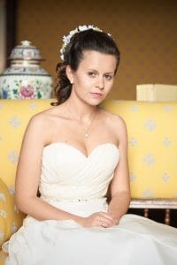 Portrait of bride on yellow sofa in Castello Dal Pozzo suite.