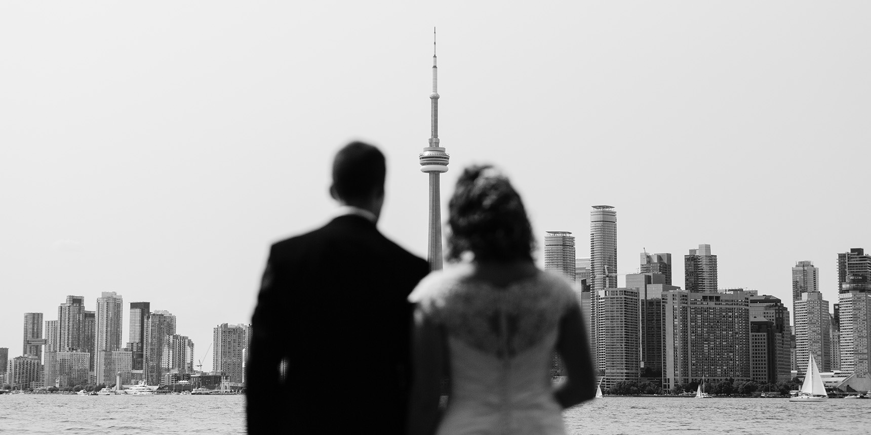 Improvised wedding photo of couple looking at downtown Toronto from across the waterfront.