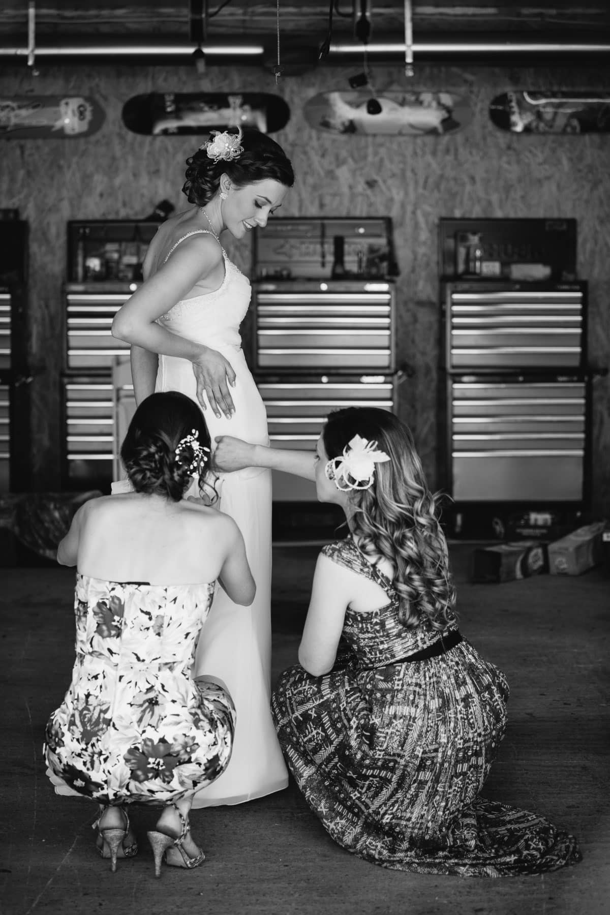 The bride is helped with her dress by two women inside a garage in these backyard wedding photos.