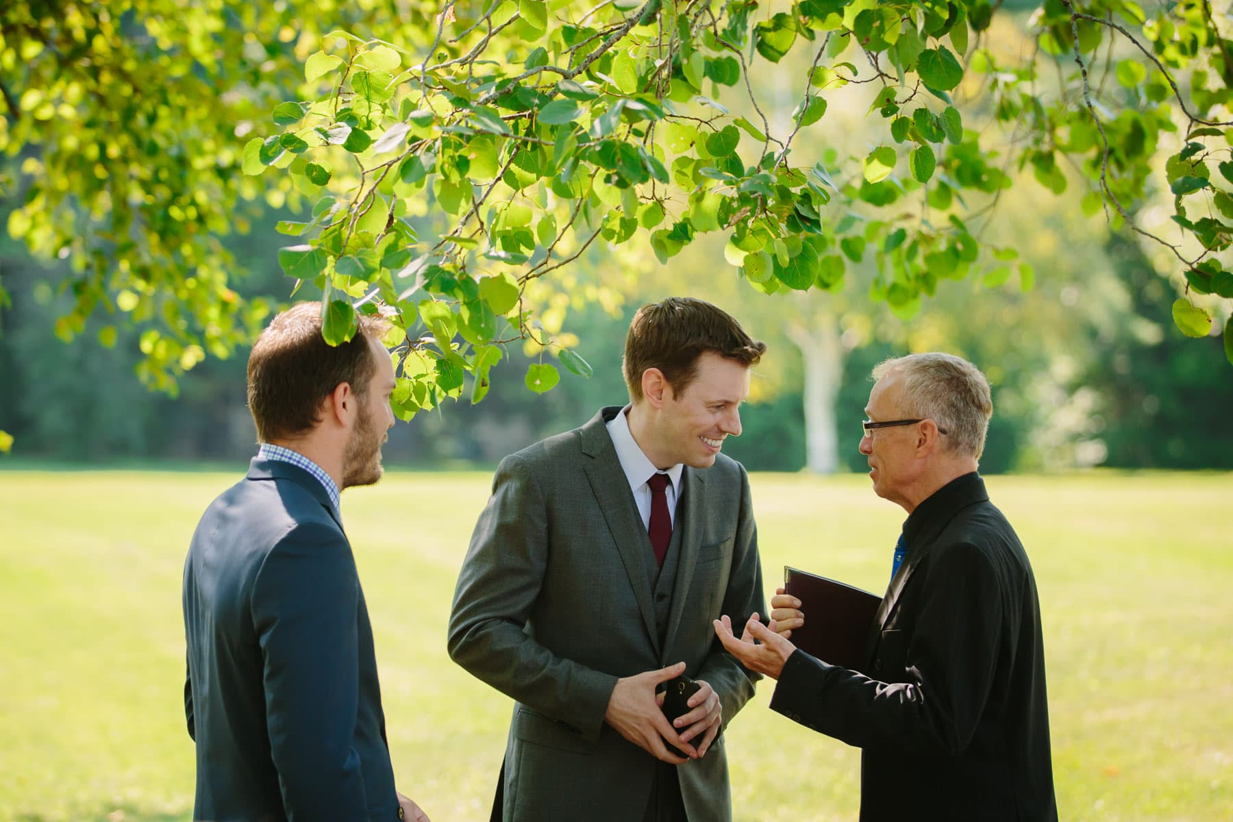 Three men, including the groom, stand in a yard underneath birch tree branches in these backyard wedding photos.