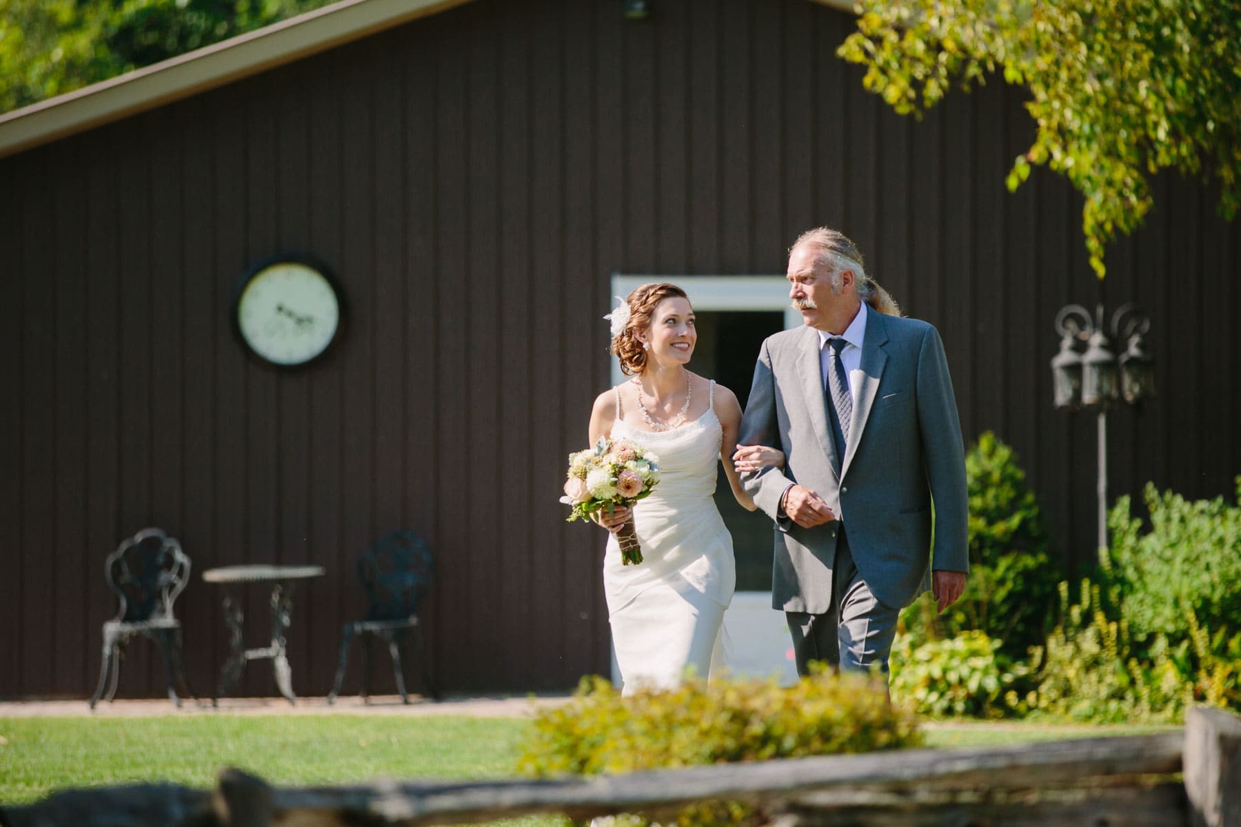 Bride looks at father as he walks her towards the wedding ceremony location in these outdoor backyard wedding photos.