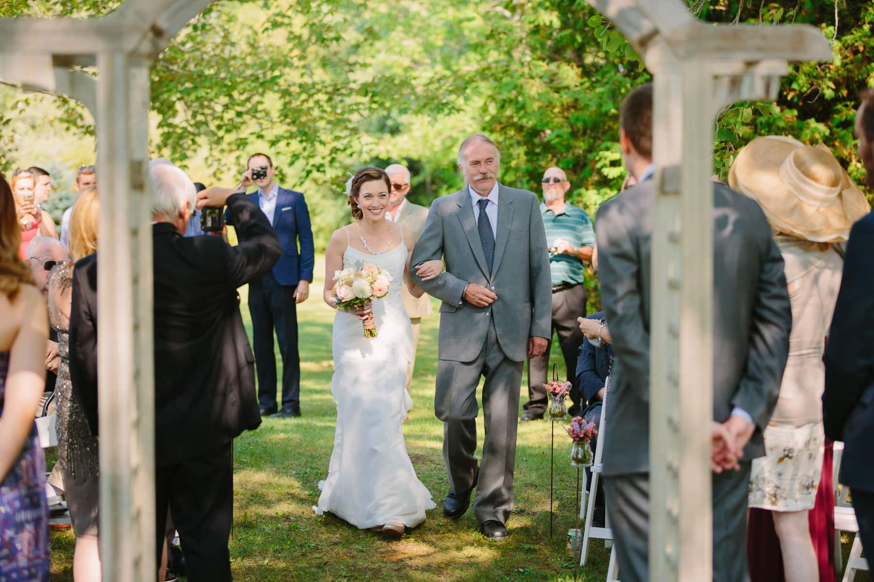 Bride is walked down aisle by moustached father in these outdoor backyard wedding photos.