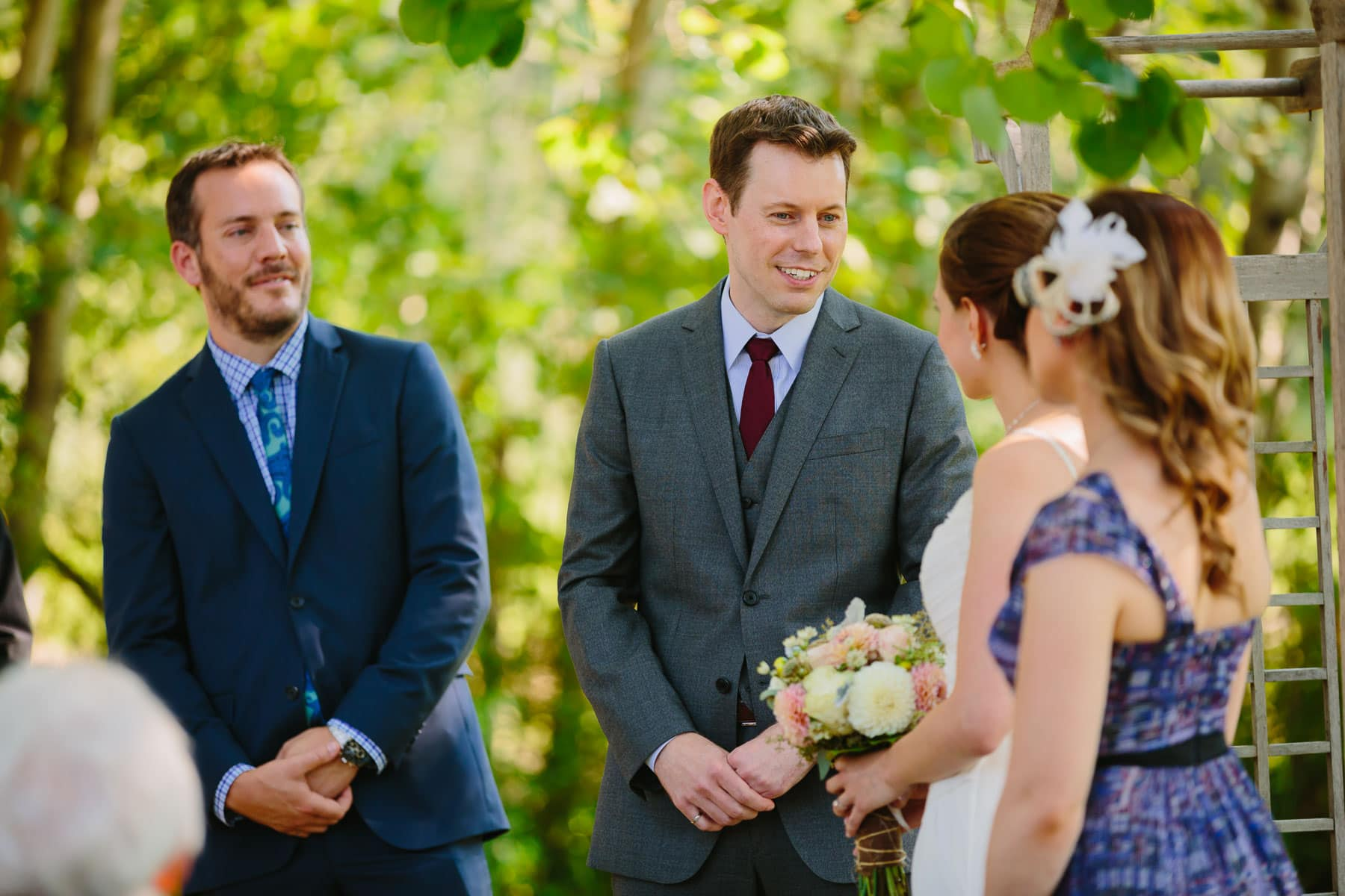 The groom speaks his vows while best man watches during ceremony in these backyard wedding photos.