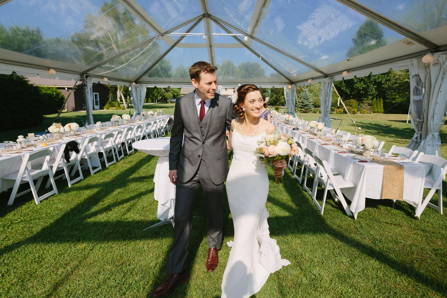 The bride and groom walk into the clear top white tent in these backyard wedding photos.
