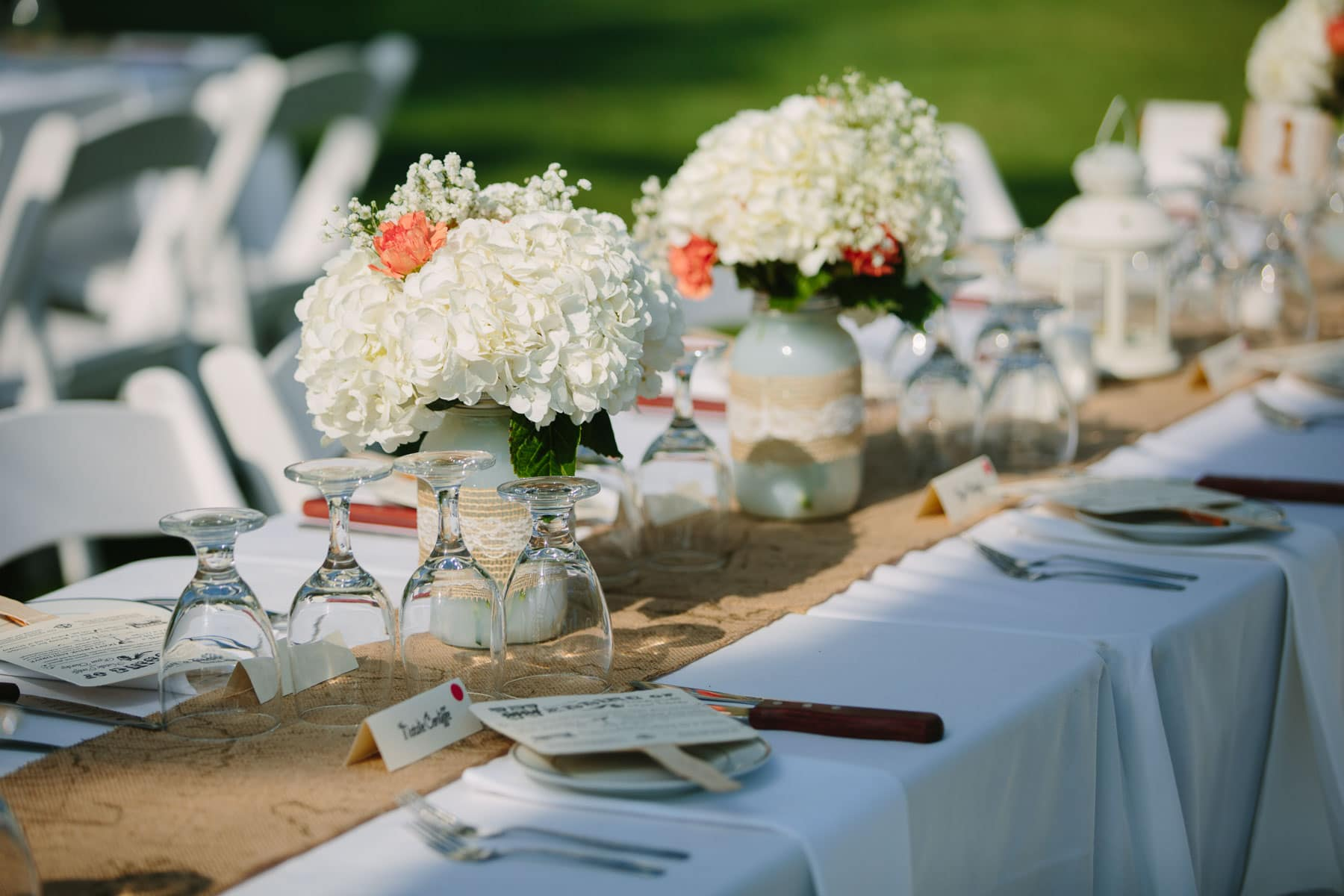 Wedding dinner decorations featuring flowers, menues on popsicle sticks, and cutlery in these backyard wedding photos.
