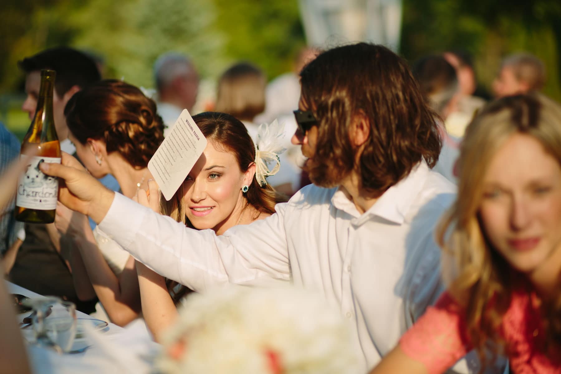 A man passes a bottle of wine and a woman uses menu to shield the sun from her eyes in these backyard wedding photos.
