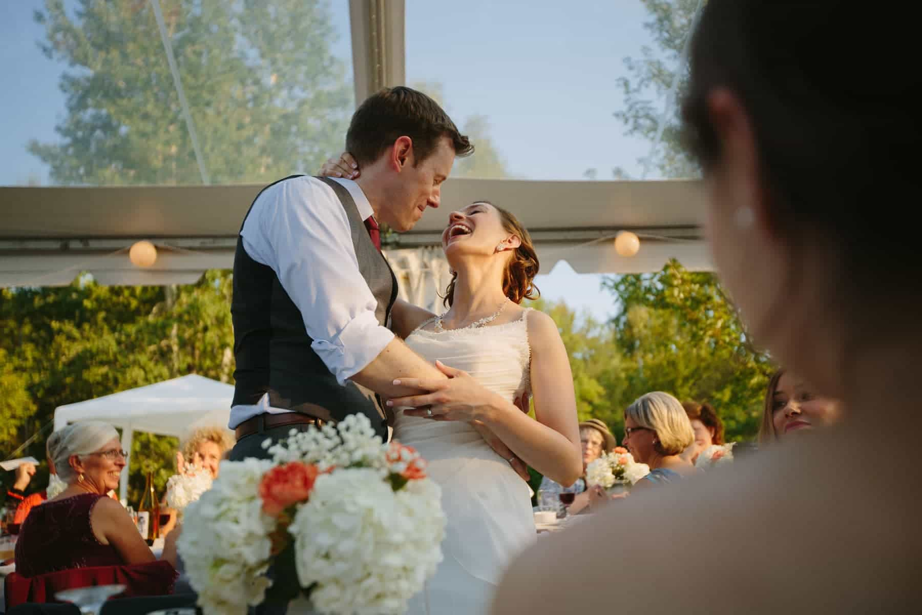 The groom bends the bride over his arm as she laughs during the summer dinner reception in a clear top tent in these backyard wedding photos.