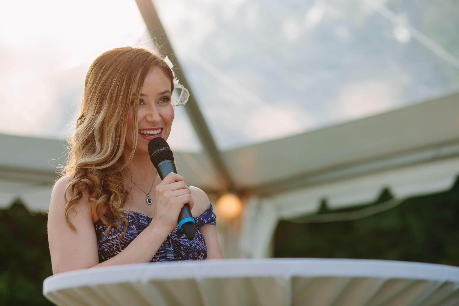 The maid of honour delivers a speech with a wireless microphone under a clear top white tent in these backyard wedding photos.