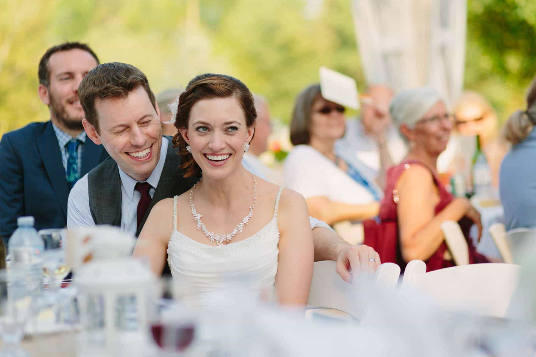 The bride and groom laugh at a speech in these backyard wedding photos.