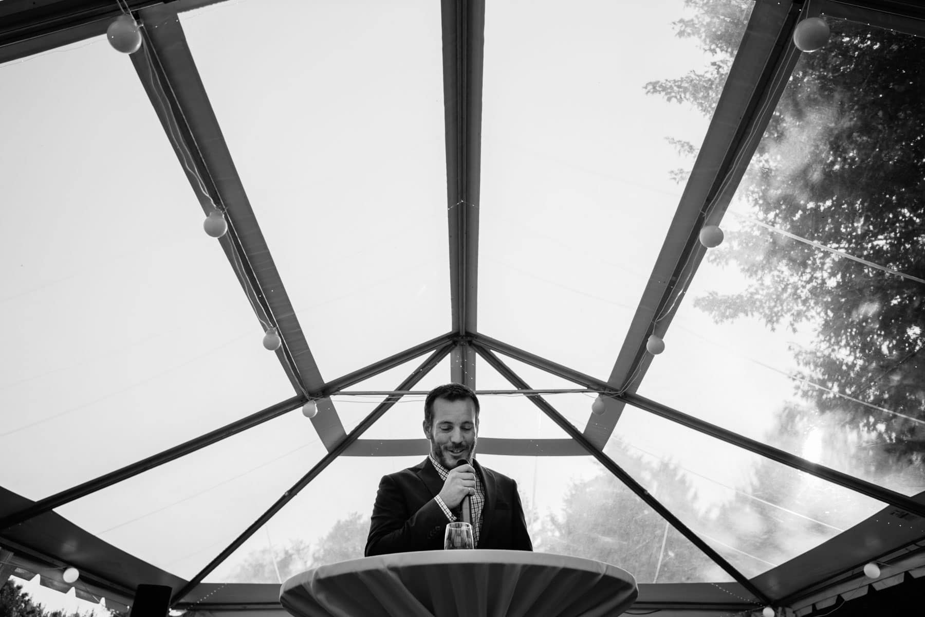 The best man delivers a wedding speech with a clear top white tent in background in these backyard wedding photos.