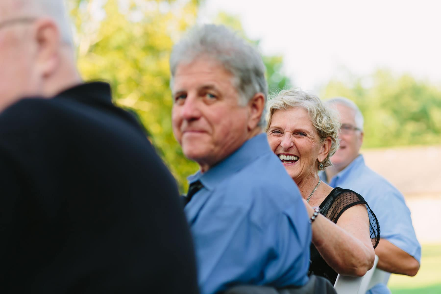 A female guest laughs during a speech in these backyard wedding photos.