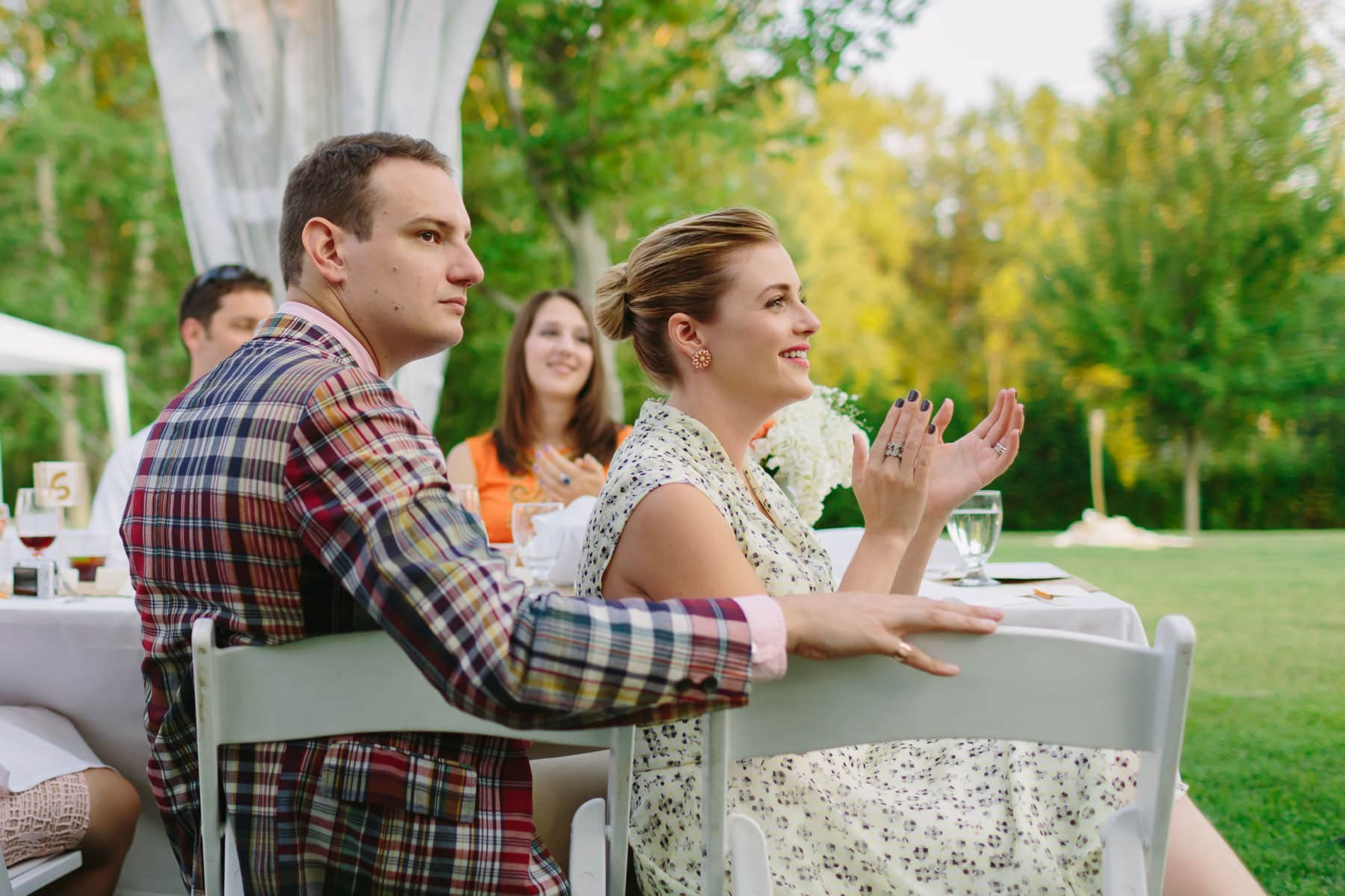 Two guests watch a speech and a woman claps in these backyard wedding photos.