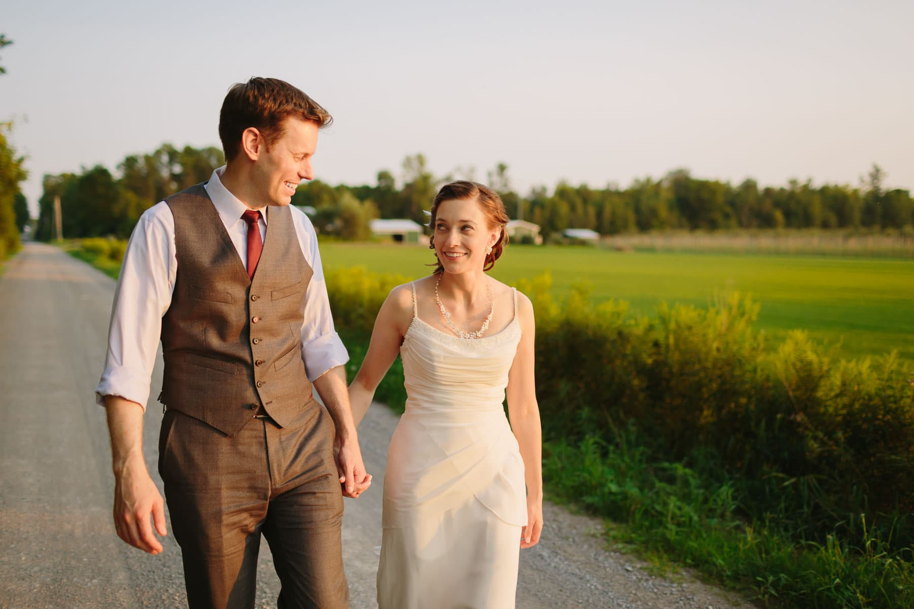 Bride and groom hold hands and look at each other as they walk down country road during sunset in these backyard wedding photos.