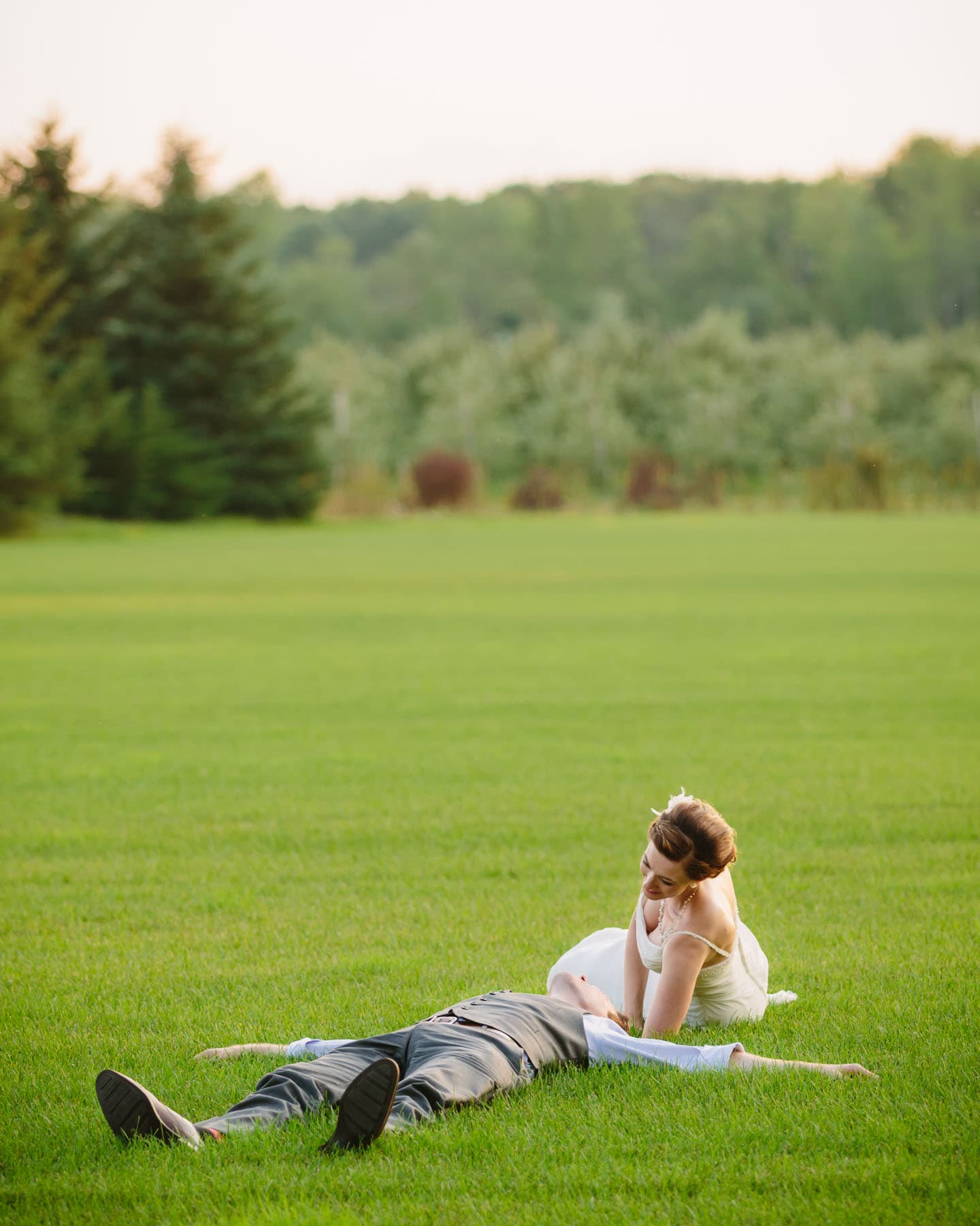 The groom is lying on his back and the bride leans over him on a sod farm in these backyard wedding photos.