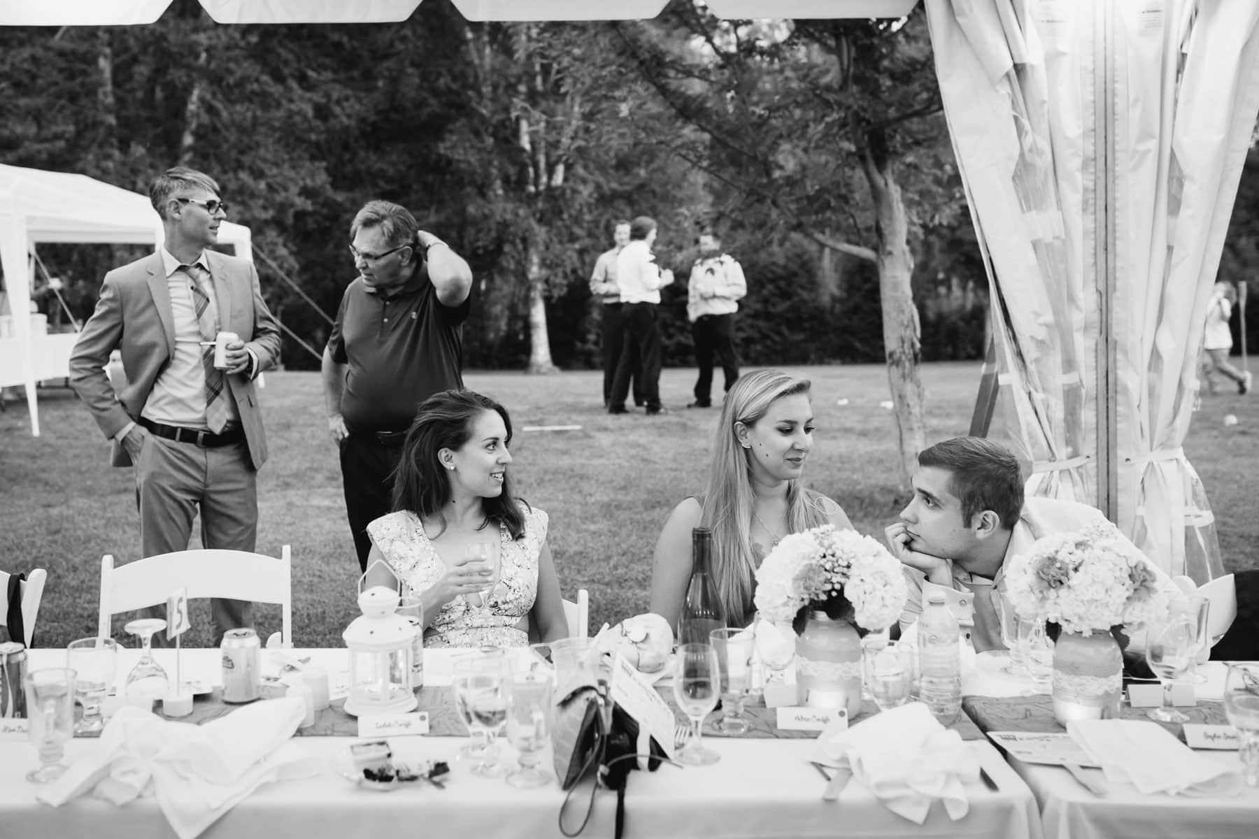 A photojournalistic moment caught between guests in deep conversation in these backyard wedding photos.