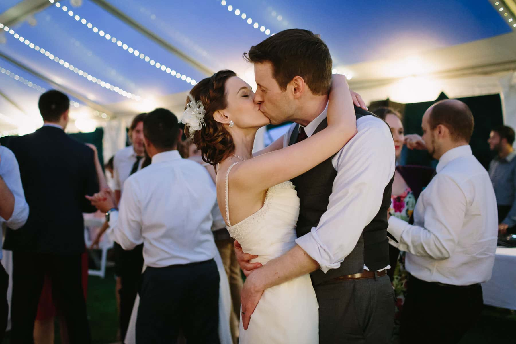 The bride and groom share a dance beneath a white tent during twilight in these backyard wedding photos.