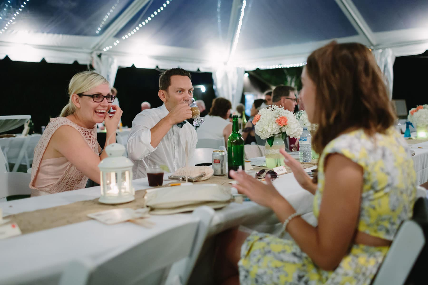 Three guests converse at a table beneath a rental tent in these backyard wedding photos.