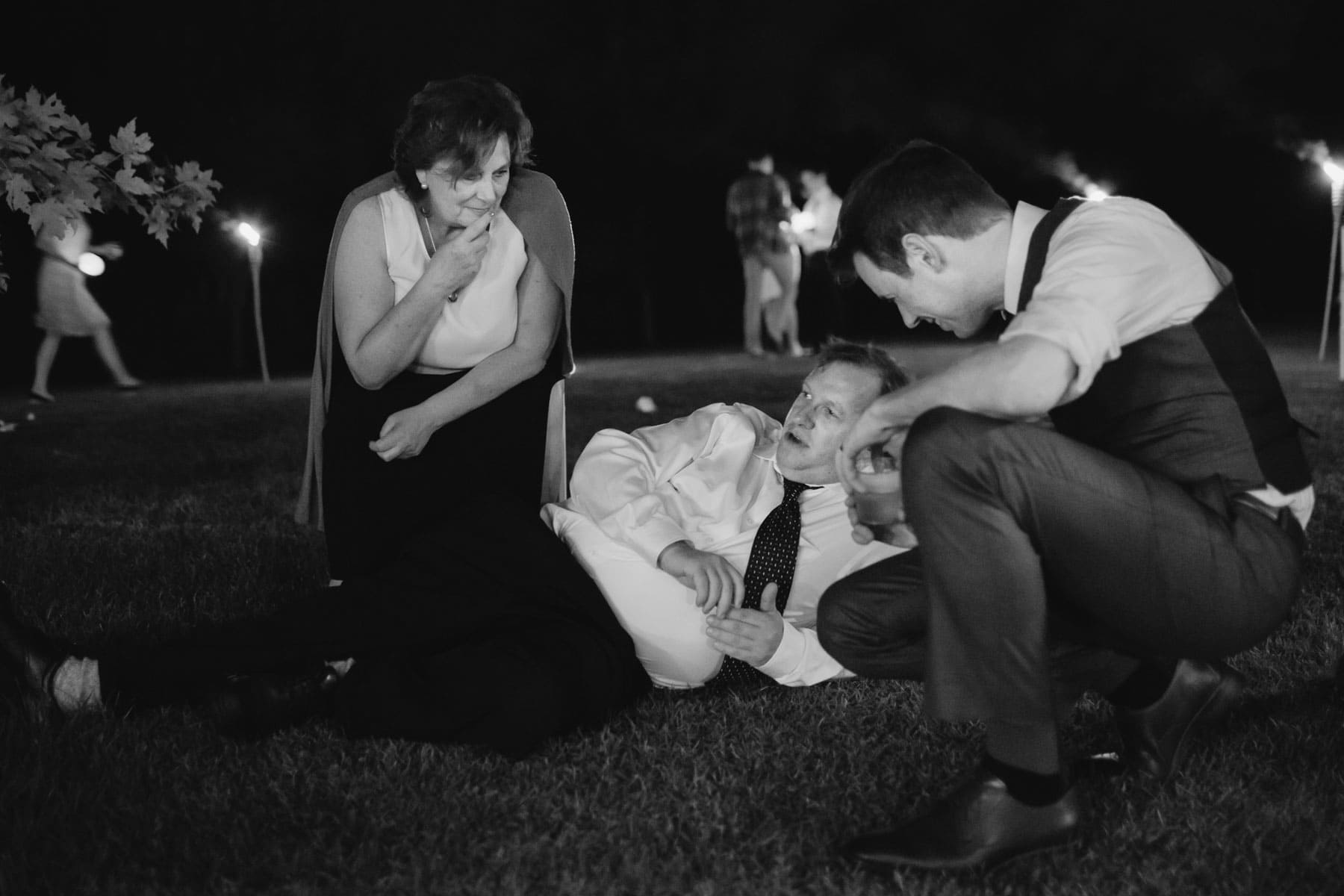 A woman, a man lying on the ground, and the groom, have a conversation in these backyard wedding photos.