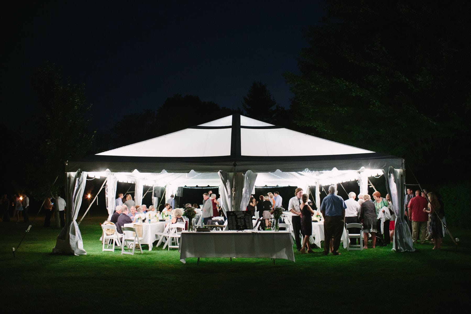 A bright temporary tent at the end of the night full of guests in these backyard wedding photos.