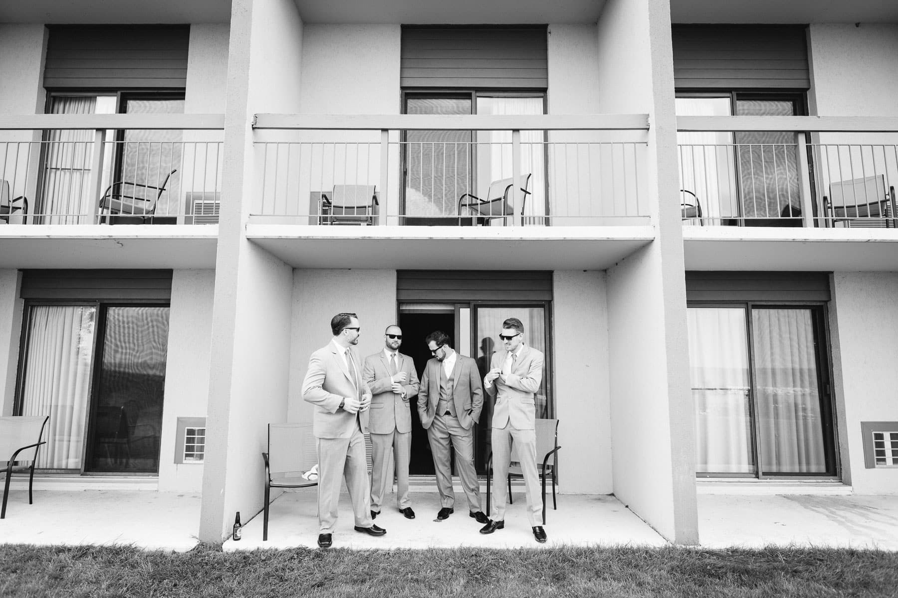 The groom and three groomsmen stand outside his hotel room at this rustic Ball's Falls wedding.