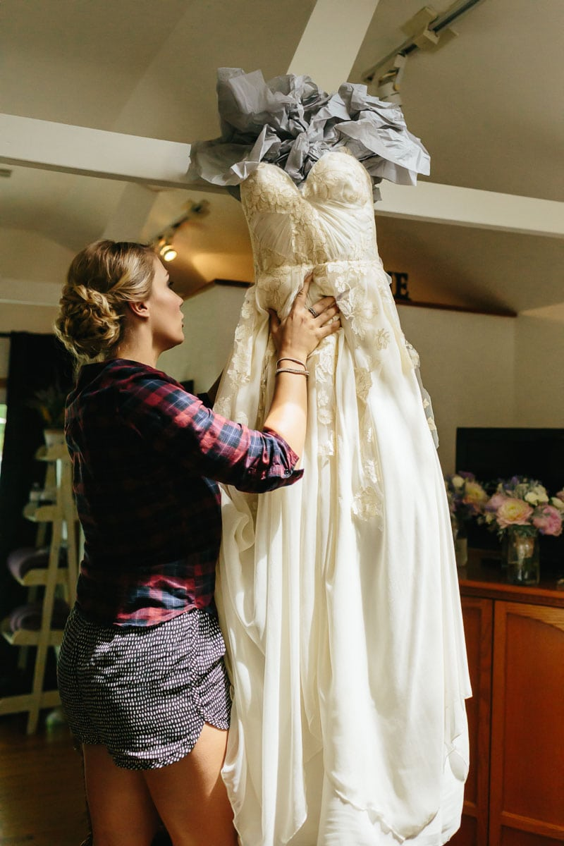Bridesmaid hanging the wedding dress in this rustic Ball's Falls wedding.