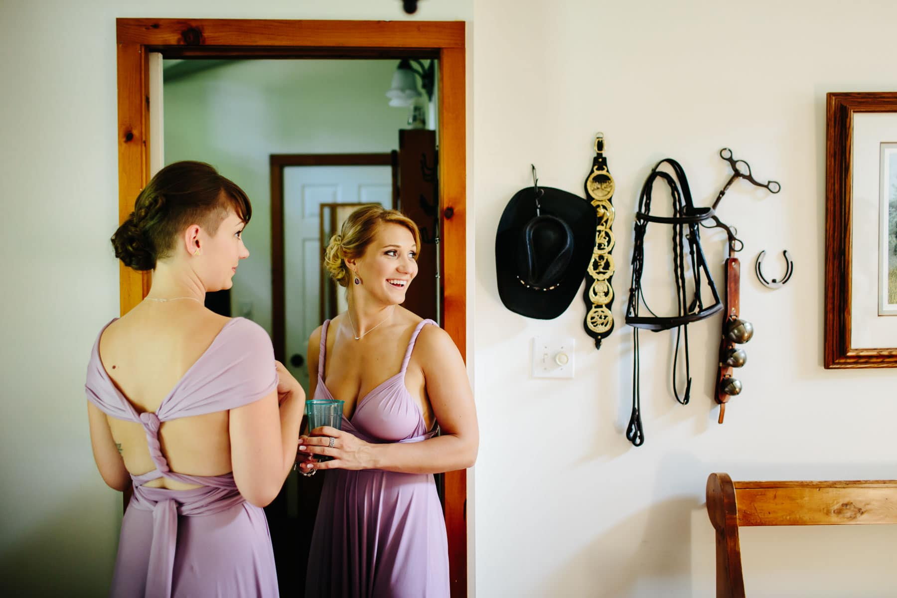 Two bridesmaids in violet dresses inside a BnB by a doorway in this rustic Ball's Falls wedding.