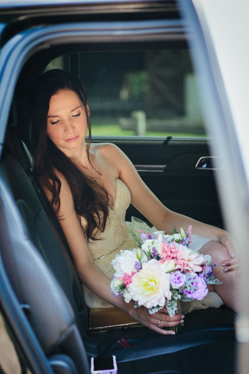 Bride sitting in the back of a white limo holding a colourful bouquet in this rustic Ball's Falls wedding.