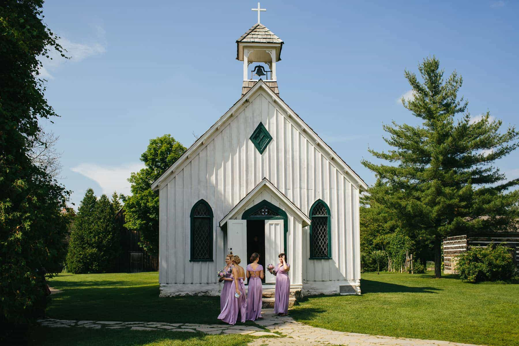 Four bridesmaids outside the front door of a white chapel at this rustic Ball's Falls wedding.