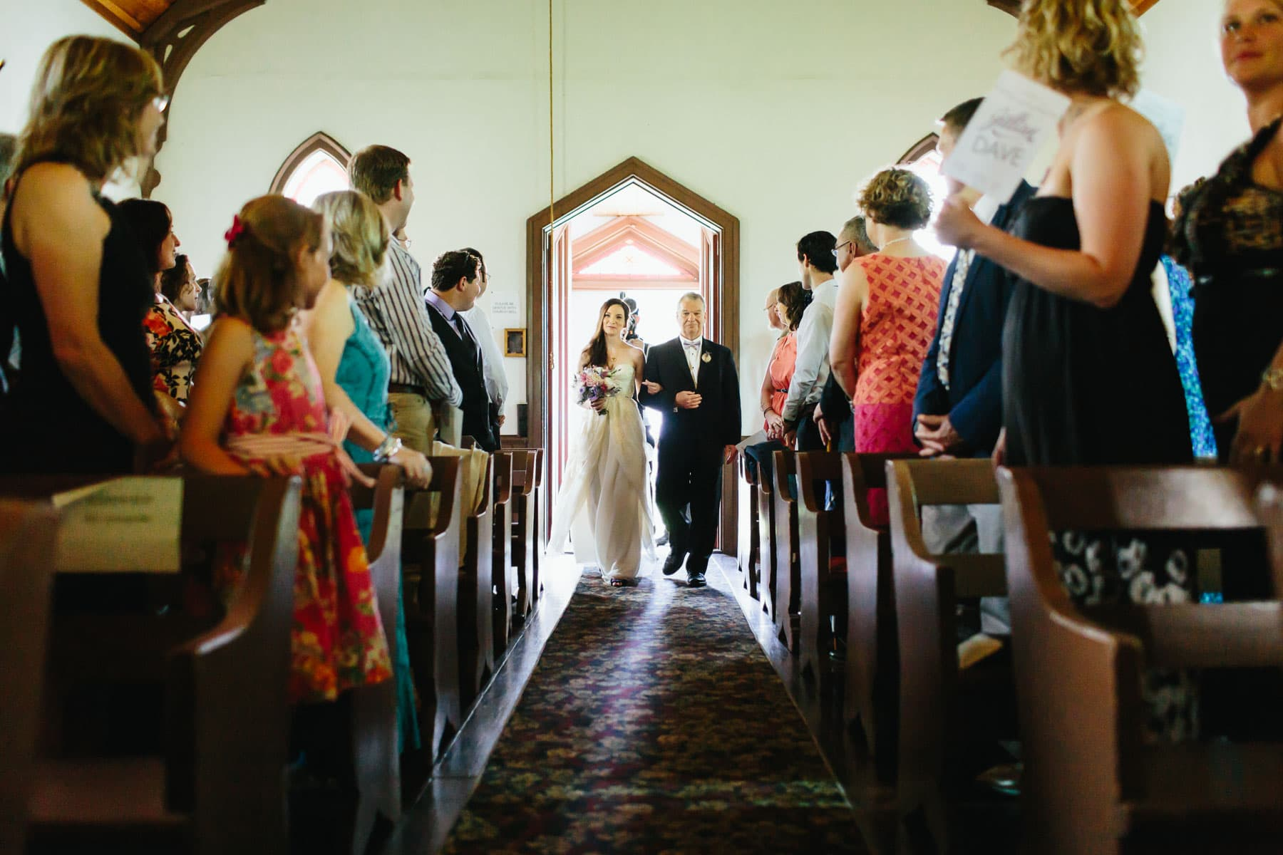 Bride and father walk down the aisle inside this small chapel at a rustic Ball's Falls wedding.