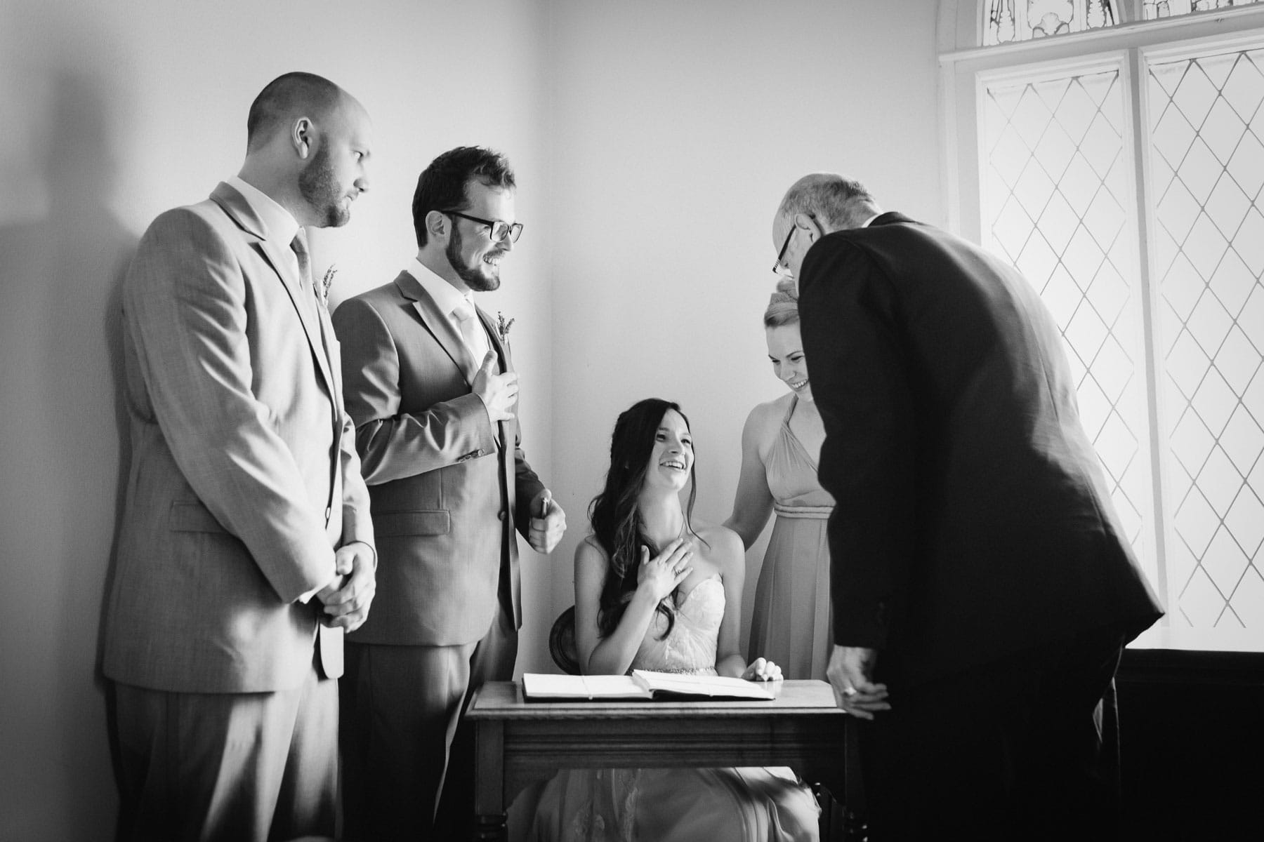 Bride and groom and witnesses signing the marriage license inside a chapel at this rustic Ball's Falls wedding.
