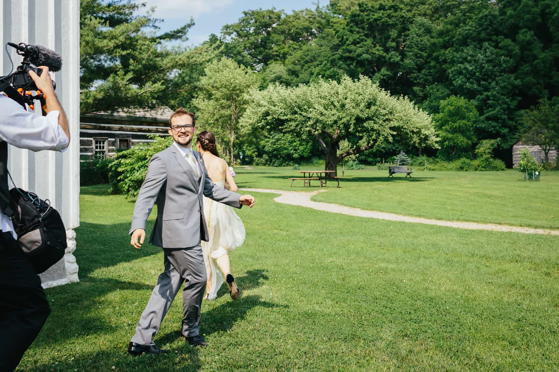 Bride and groom walking away from the videographer right after the ceremony at this rustic Ball's Falls wedding.