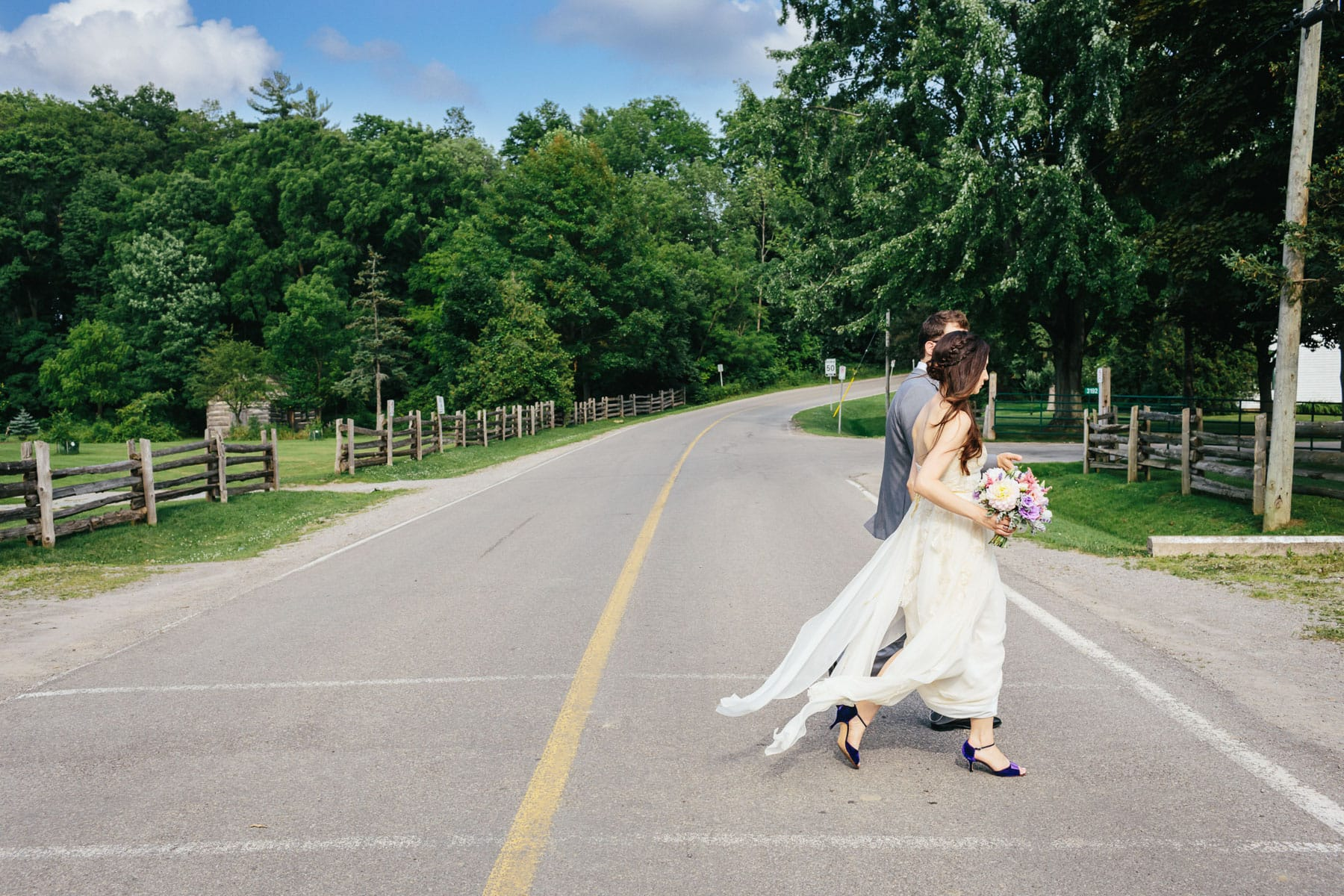 Bride and groom crossing a rural road in this rustic Ball's Falls wedding.