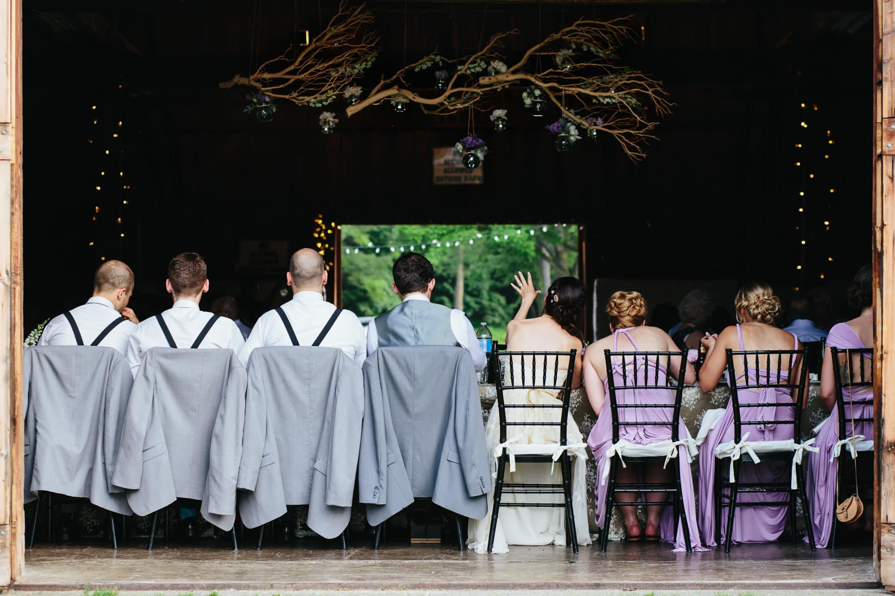 The bride, groom, and wedding party seated in a row during the dinner reception with a large decorative branch overhead at this Ball's Falls wedding.