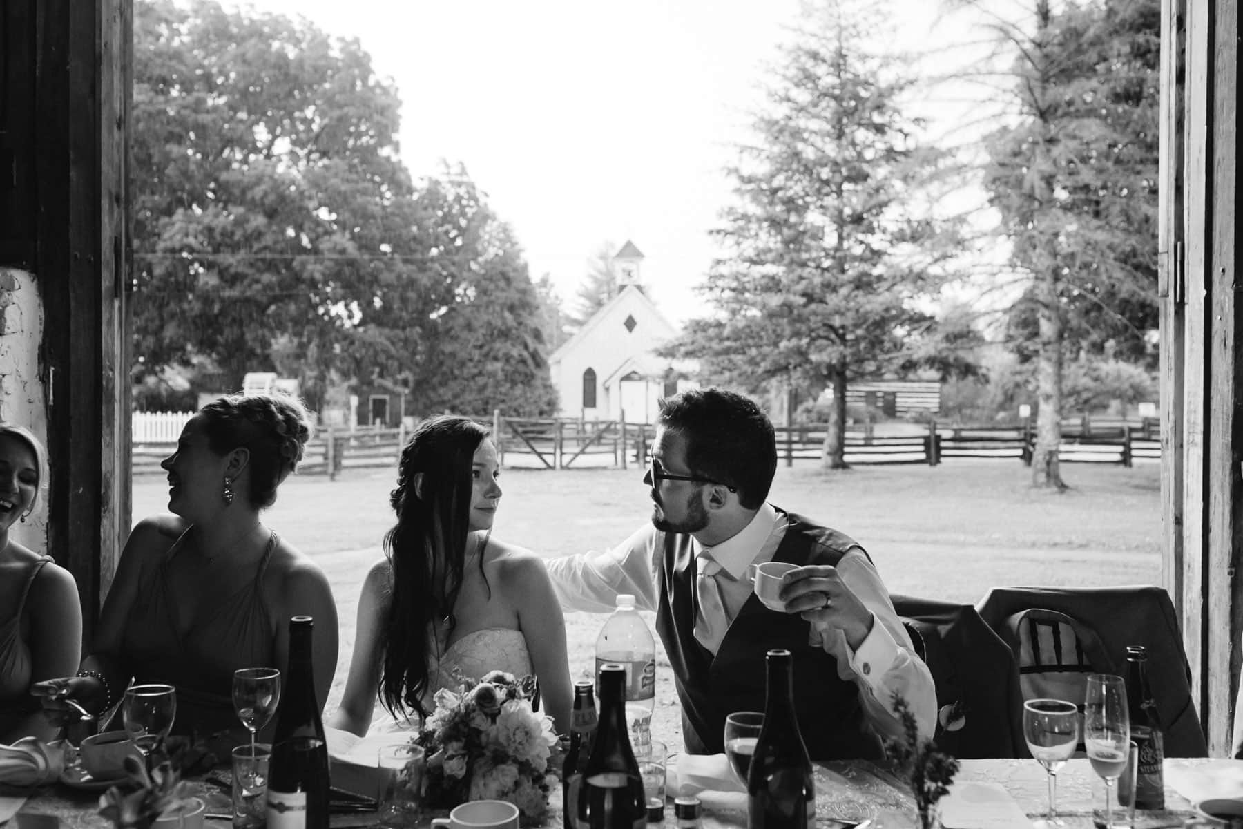 The bride and groom talk to one another at the dinner table with a white chapel in the distance at this Ball's Falls, Ontario wedding.
