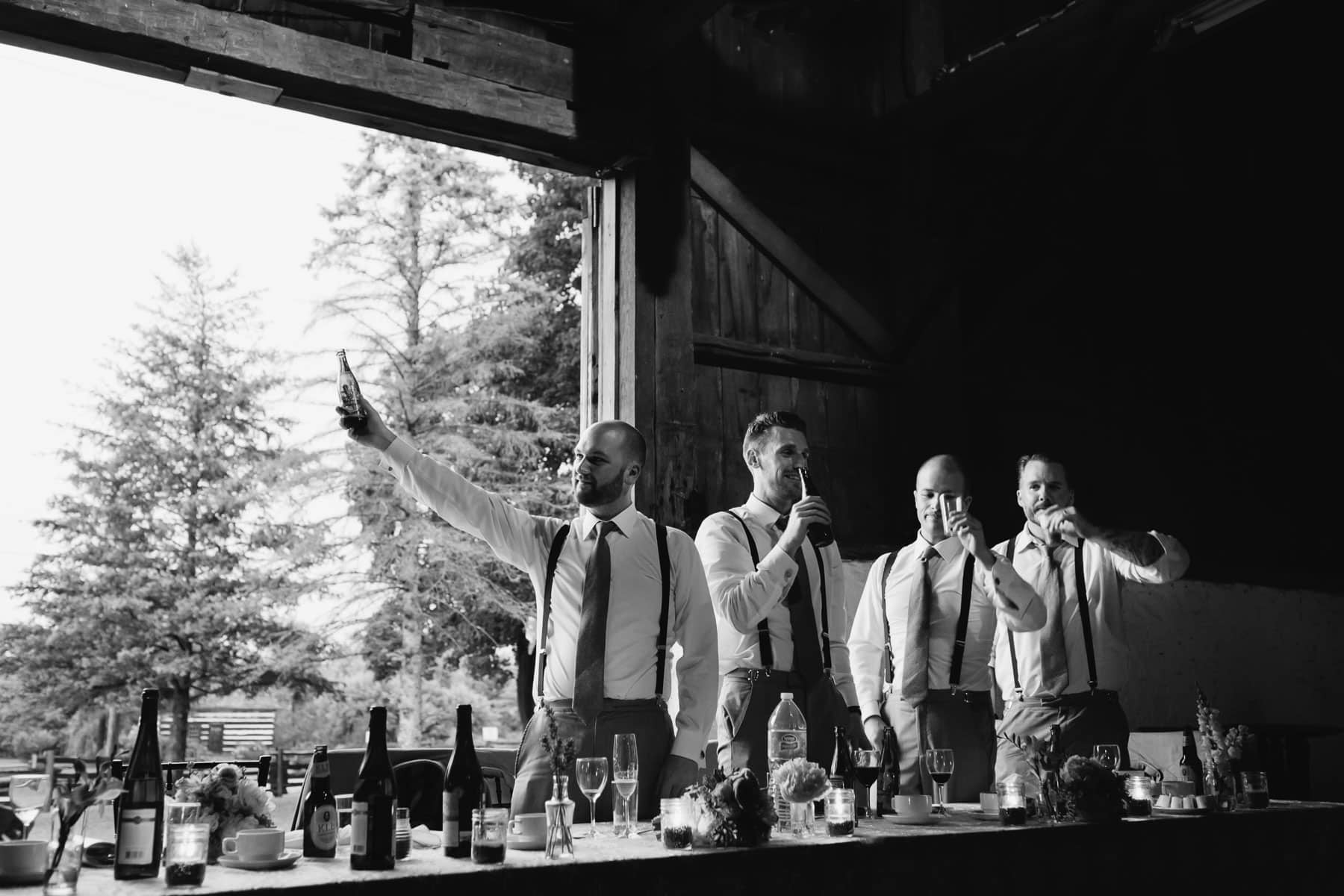 The groomsmen toast the bride and groom during their speech in a barn at this Ball's Falls, Ontario wedding.