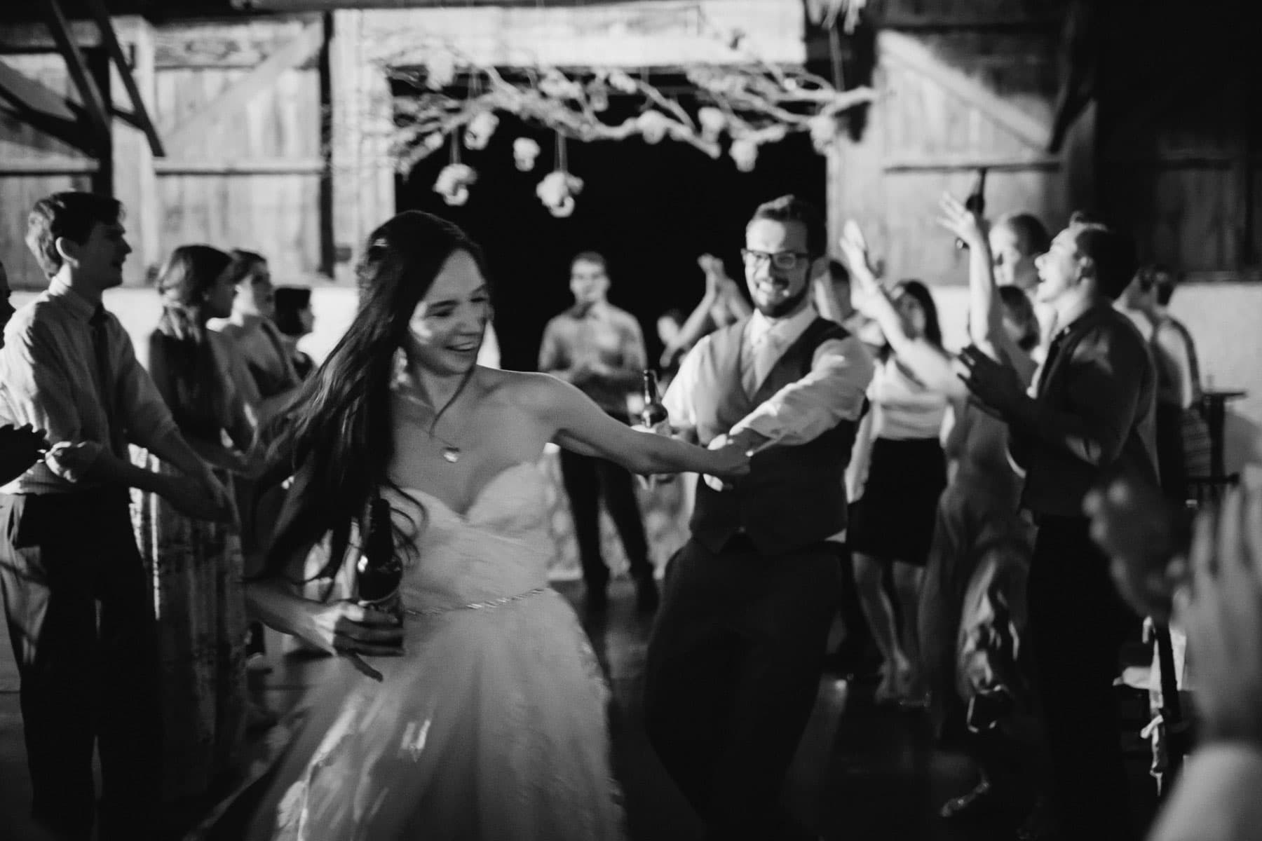 The brand and groom dance to rock music surrounded by guests in a barn at this Ball's Falls wedding.