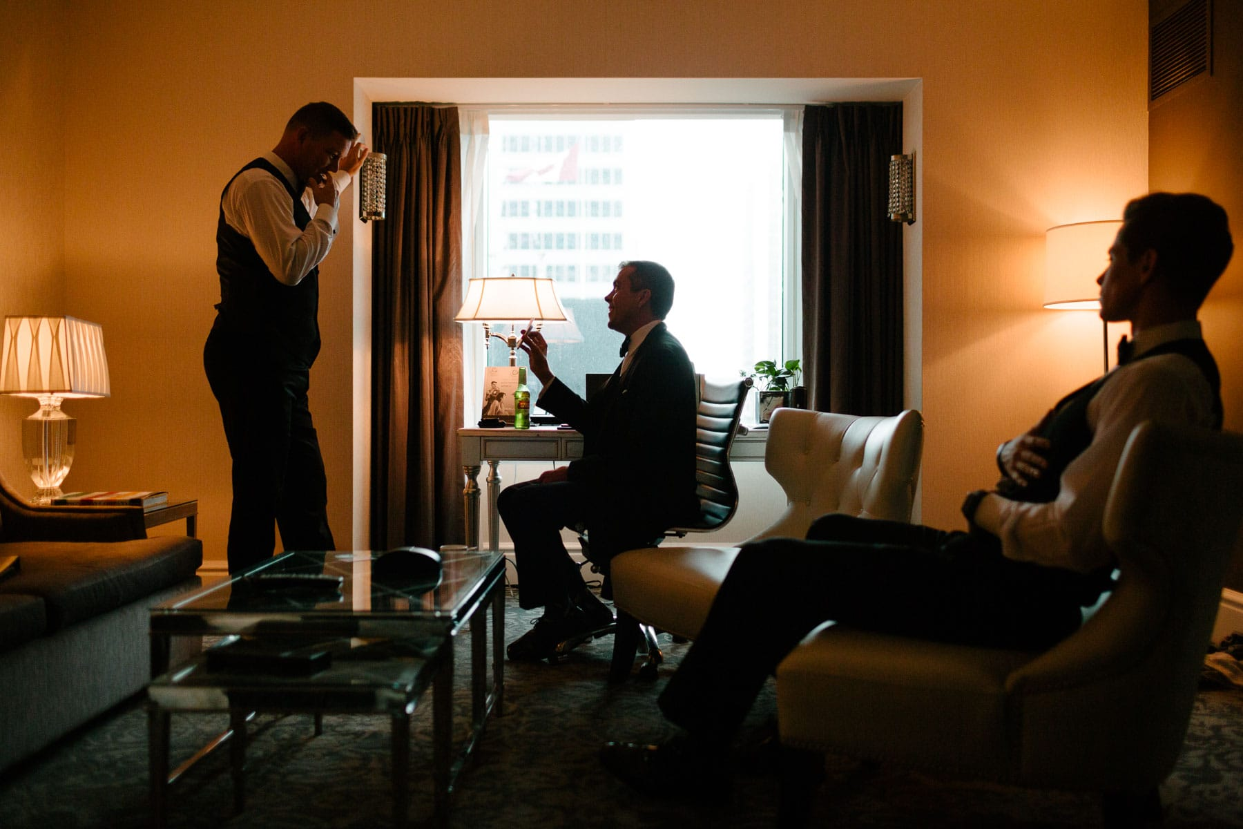 The groom is silhouetted against a bright window while talking to his friend at the Trump Hotel in Toronto.