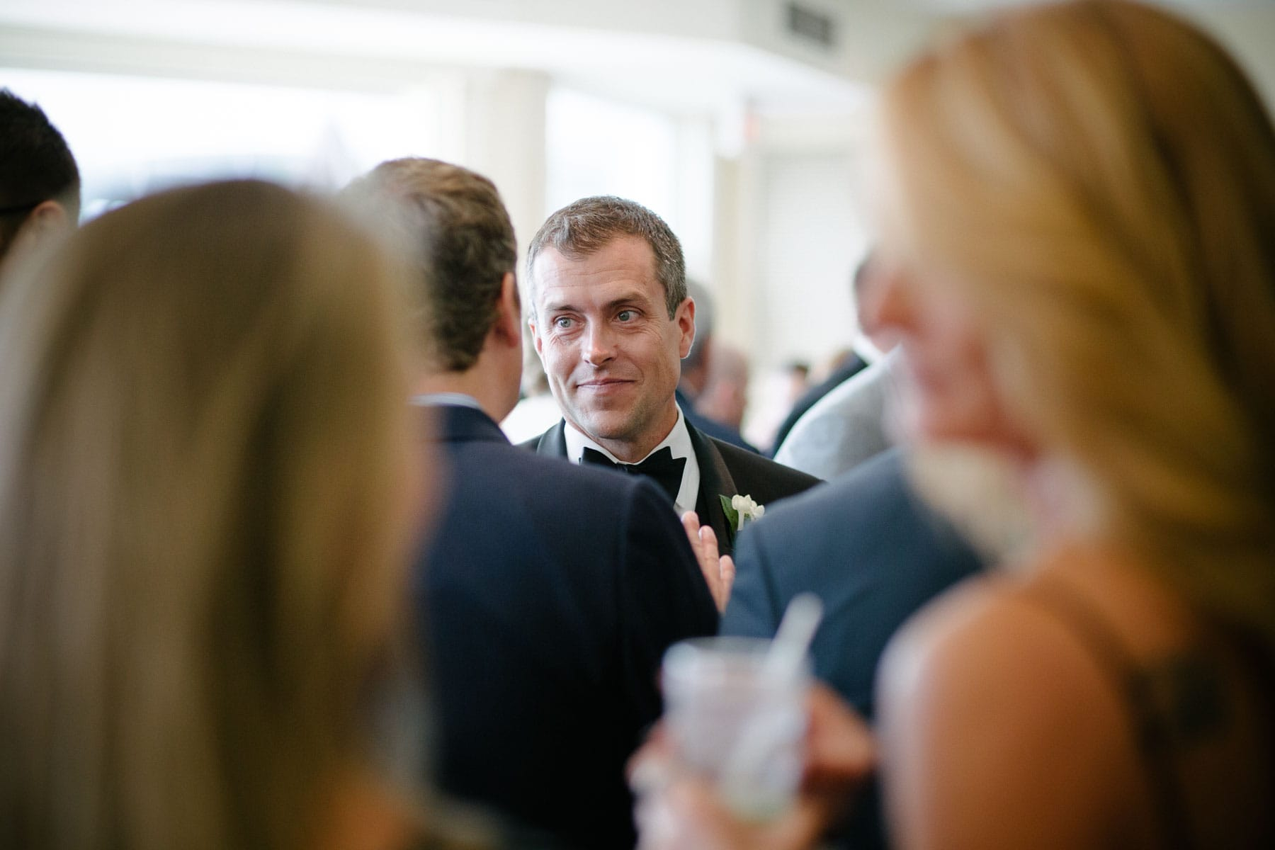 A portrait of the groom smiling at a man while surrounded by guests at this Boulevard Club wedding in Toronto.