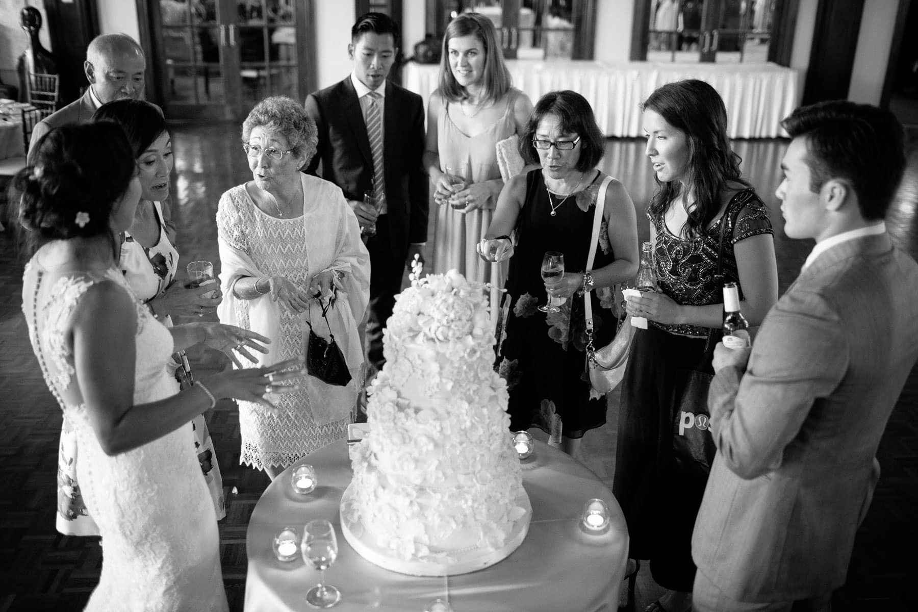 The bride and several of her family members inspect the wedding cake at the Boulevard Club wedding in Toronto.