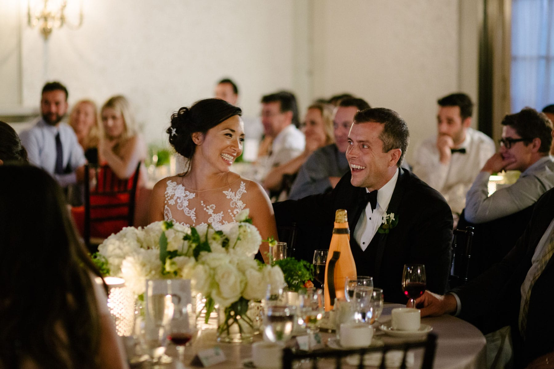 The bride and groom laugh while seated at a dinner reception table at this Boulevard Club wedding in Toronto.