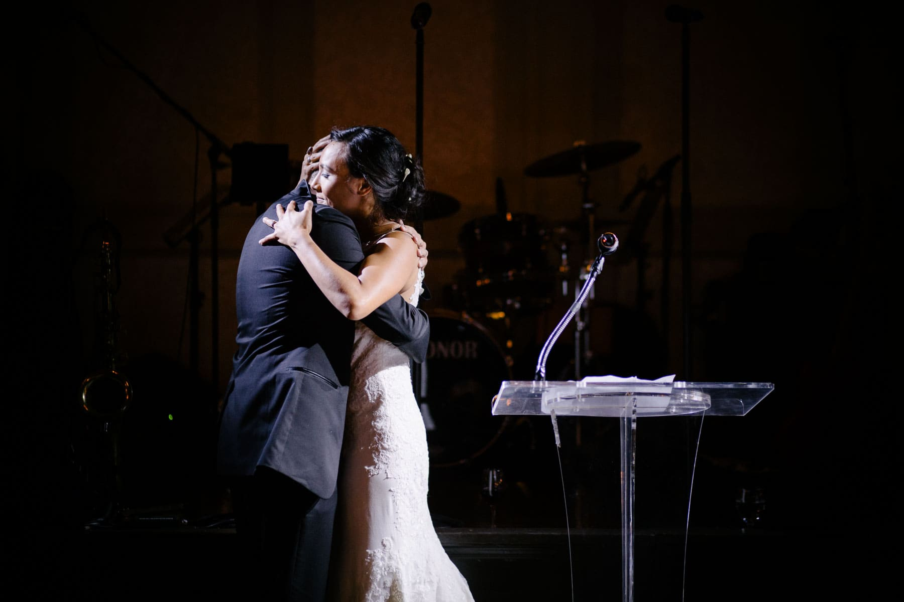 The bride and groom hug beside a speaker's pedestal in a dark room in this Boulevard Club wedding in Toronto..