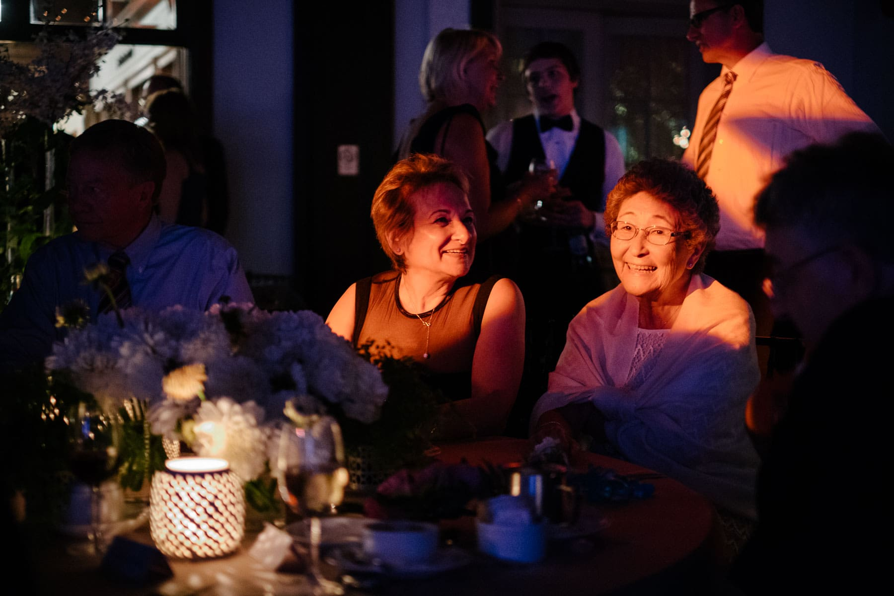 Two elderly ladies are smiling with orange light shined on them at the Boulevard Club wedding in Toronto.
