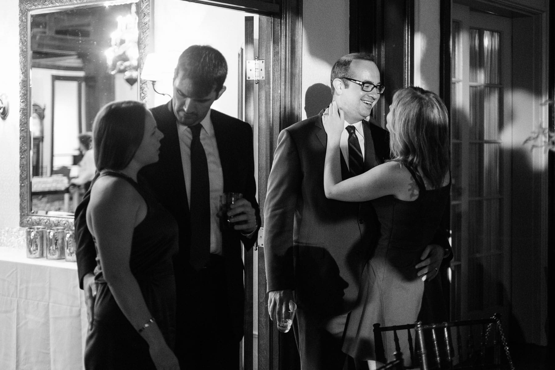 Two pairs of guests share an intimate moment by a door at the Boulevard Club wedding.