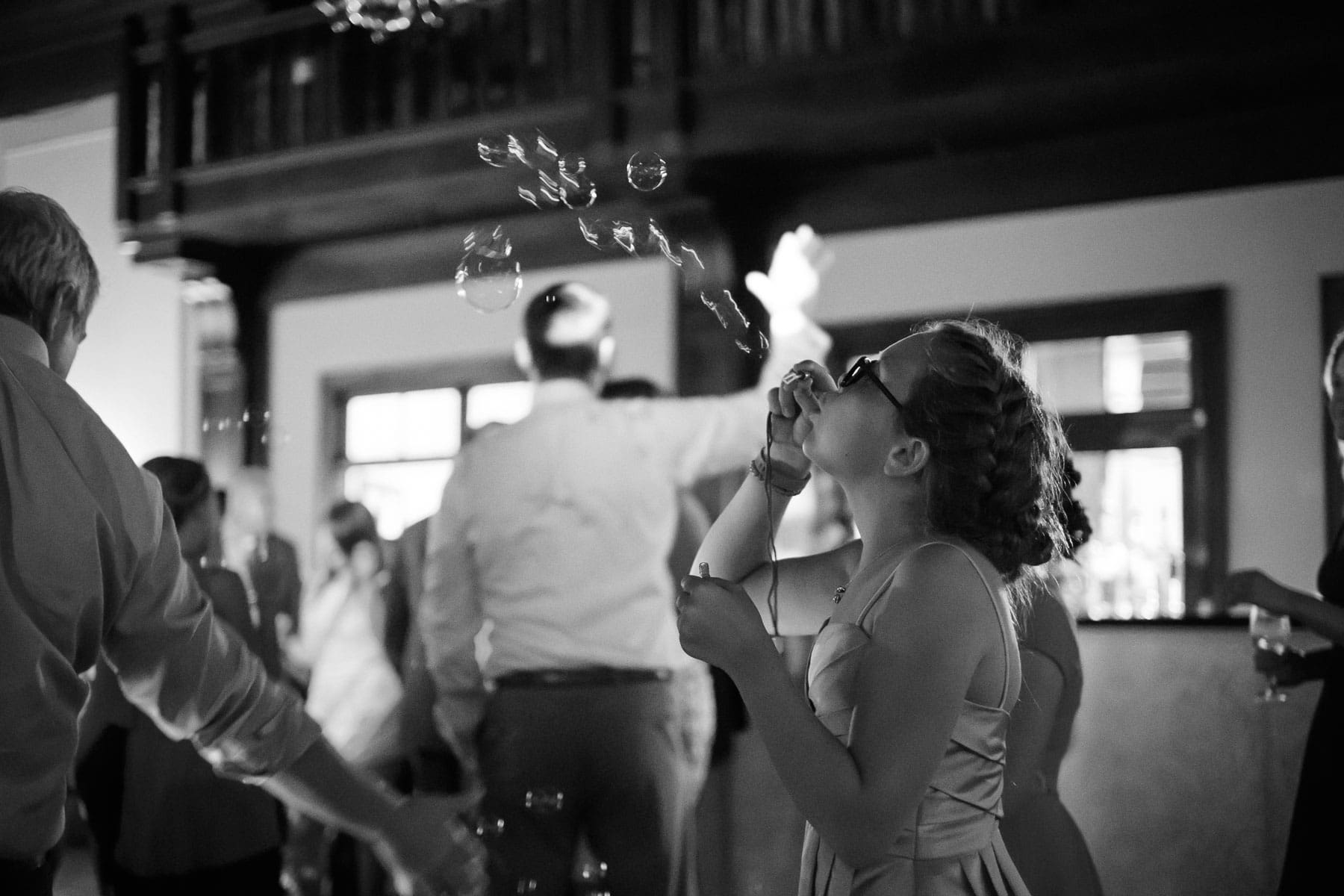 A girl blows soap bubbles up into the air on the dancefloor at this Boulevard Club wedding.