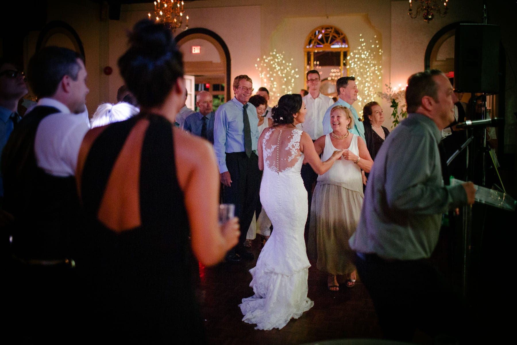 The bride dances with an older woman on the crowded dance floor at the Boulevard Club wedding.