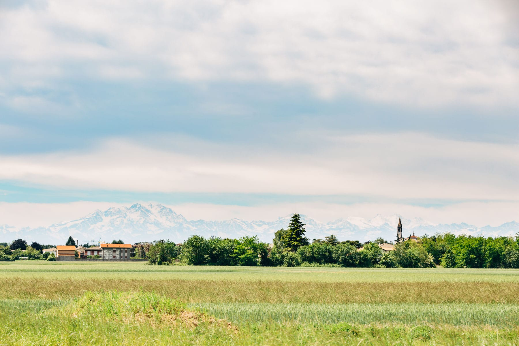 A pastoral scene of the northern Italian countryside with the Alps in the distance at this Italian destination wedding in Castello Dal Pozzo.