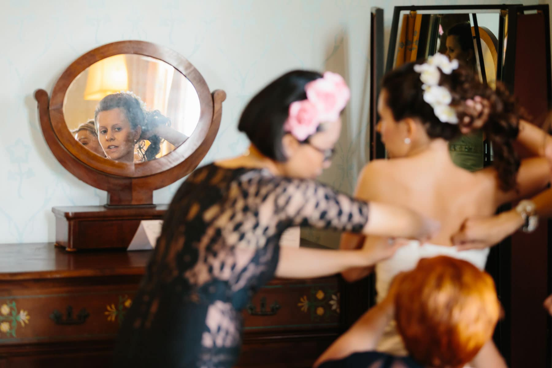 The bride checks herself out in a small round mirror as several women help her with the wedding dress in this Italian destination wedding in Castello Dal Pozzo.