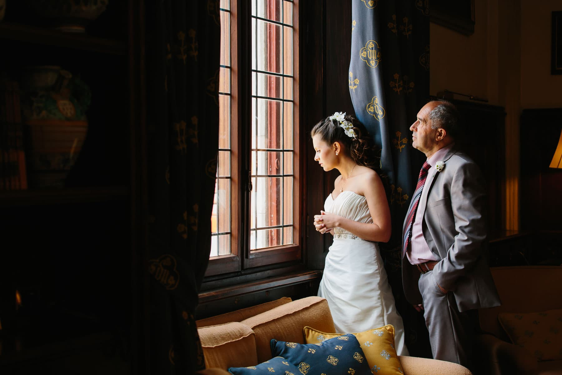 Window light illuminates the bride and her father as they peer towards the courtyard in this Italian destination wedding in Castello Dal Pozzo.
