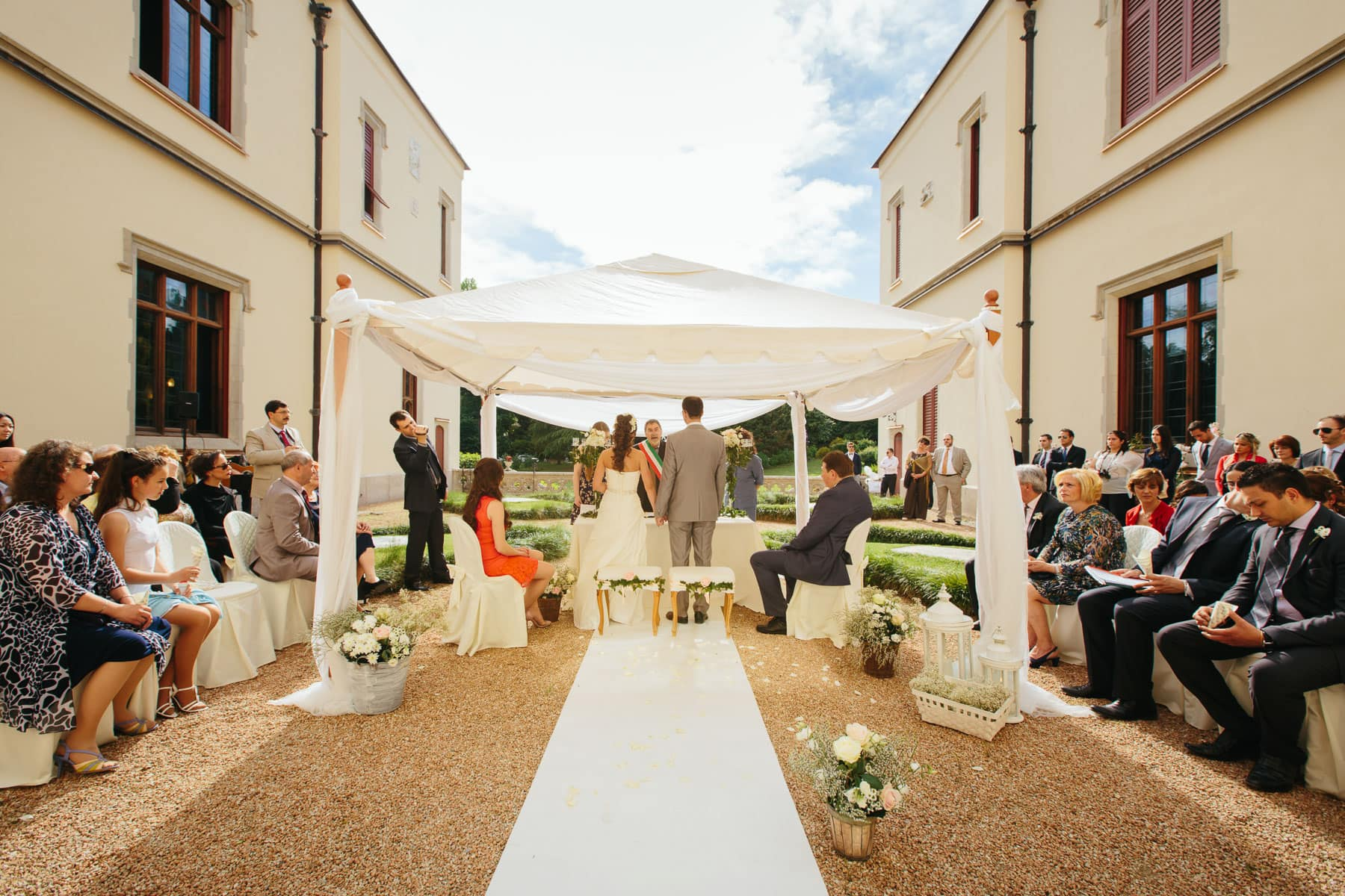 The bride and groom stand beneath a white tent during the ceremony with guests seating around them in the courtyard during a Italian destination wedding in Castello Dal Pozzo.